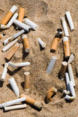 Cigarette butt in sand — Stock Photo