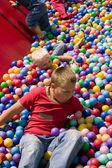 Chlapci hrají v bazénu barevné koule — Stock fotografie
