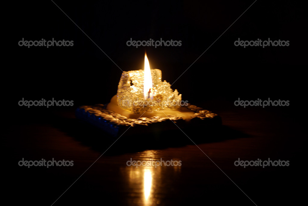 A lighted candle and its reflection in the dark surface — Stock Photo #2504216