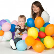 Mother and son playing party balloons - Stock Photo