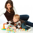 Mother and son playing wooden cubes — Stock Photo