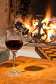 Red wine and fireplace — Stock Photo