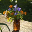 Small bouquet in brown glass — Stock Photo
