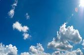 Blue cloudy sky with sun panorama — Stock Photo
