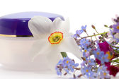 Cosmetic cream with flowers — Stock Photo