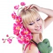 Young blond girl with pink orchid — Stock Photo