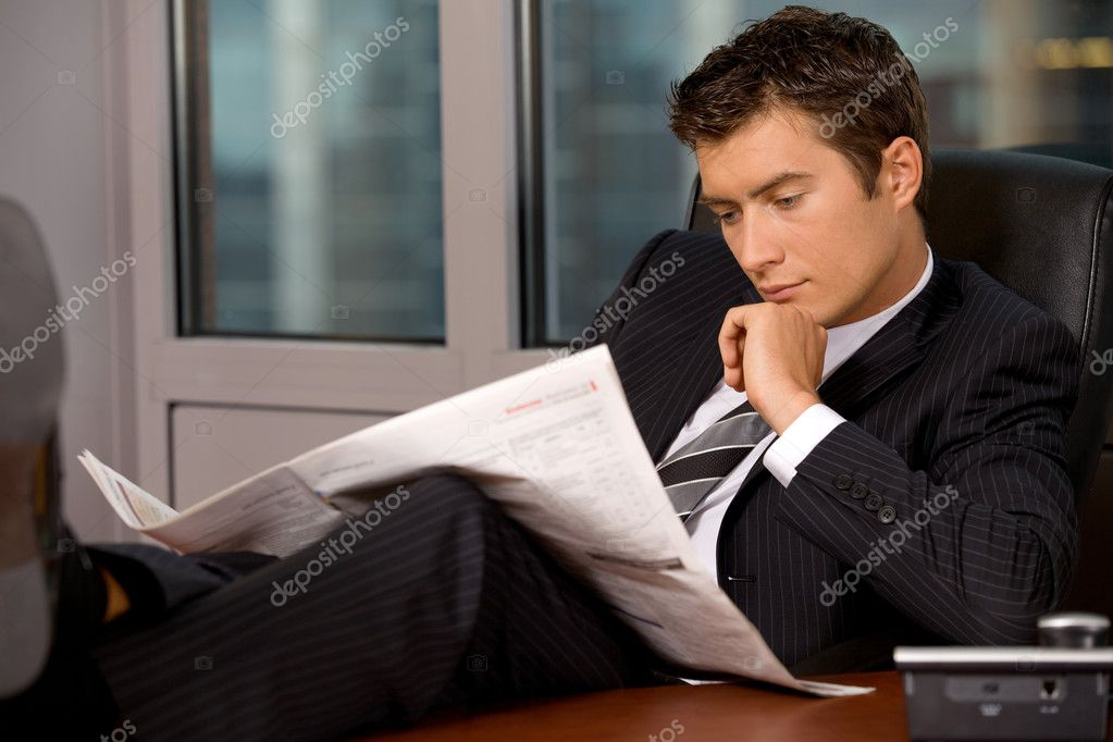 Businessman reading newspaper in office with hand on chin — Stock Photo #2419288