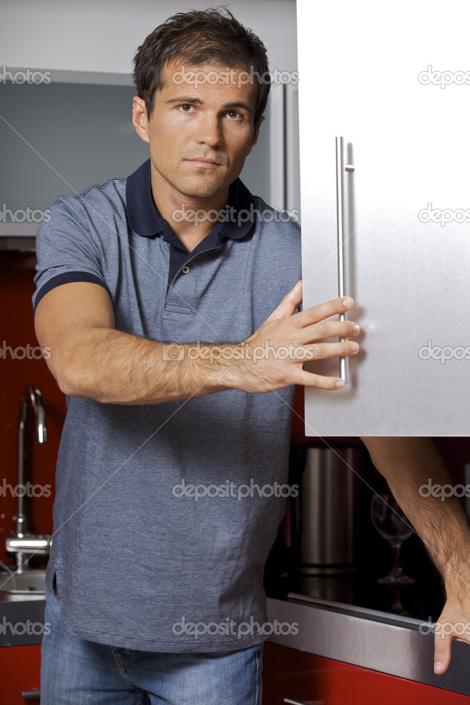 Portrait of young man opening door of cabinet  Stock Photo #2420094