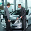 Car salesperson explaining car features to customer - Photo