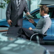 Car salesperson giving catalog to businessman — Stock Photo
