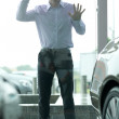 Young man curiously looking at new car in showroom — Stok fotoğraf