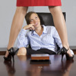 Businesswoman standing on table in front of businesswoman at office — Stock Photo