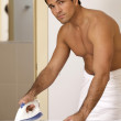 Portrait of man in towel ironing clothes on a st — Stock Photo