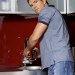 Portrait of young man washing his hands in sink — Stock Photo
