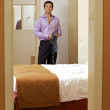 Portrait of young man holding tie in hotel room — Stock Photo