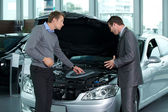 Car salesperson explaining about car's engine to — Stock Photo