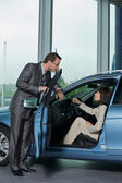 Car salesperson explaining car features to custo — Stock Photo