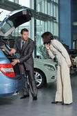Car salesperson showing car features to customer — Stock Photo