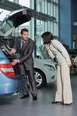 Venditore auto mostrando caratteristiche auto al cliente — Foto Stock