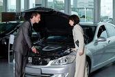 Car salesperson explaining about car — Stock Photo