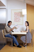 Portrait of woman sitting on breakfast table while man reading newspaper — Stock Photo