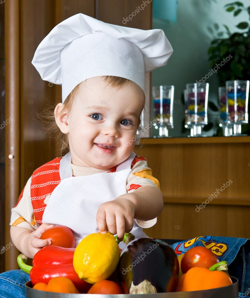 Baby in the cook costume in the white hat with vegetables — Stock Photo #2392714