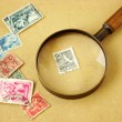Stock Photo: Postage stamps and magnifying glass