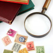 Postage stamps and magnifying glass — Stock Photo
