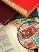 Magnifying glass and postage stamps — Stock Photo