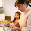Stock Photo: Little girl helping Mom cook