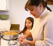 Little girl helping Mom cook — Stock Photo