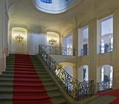 Ancient staircase with red carpet — Stock Photo