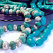 Turquoise beads on deep-blue glass plat — Stock Photo