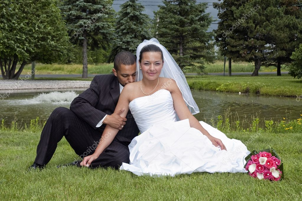 Just married multi ethnic couple sitting in the grass — Stock Photo #2601948