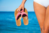 Woman holding a pair of flip flops — Stock Photo