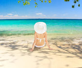 Woman sitting at tropical sea shore. — Stock Photo
