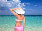 Woman with hat standing on the beach — Stock Photo