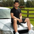 Man sit bonnet silver car in countryside - Stock Photo