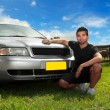 Man beside car in afternoon sun - Stock Photo