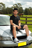 Man sit bonnet silver car in countryside — Stock Photo