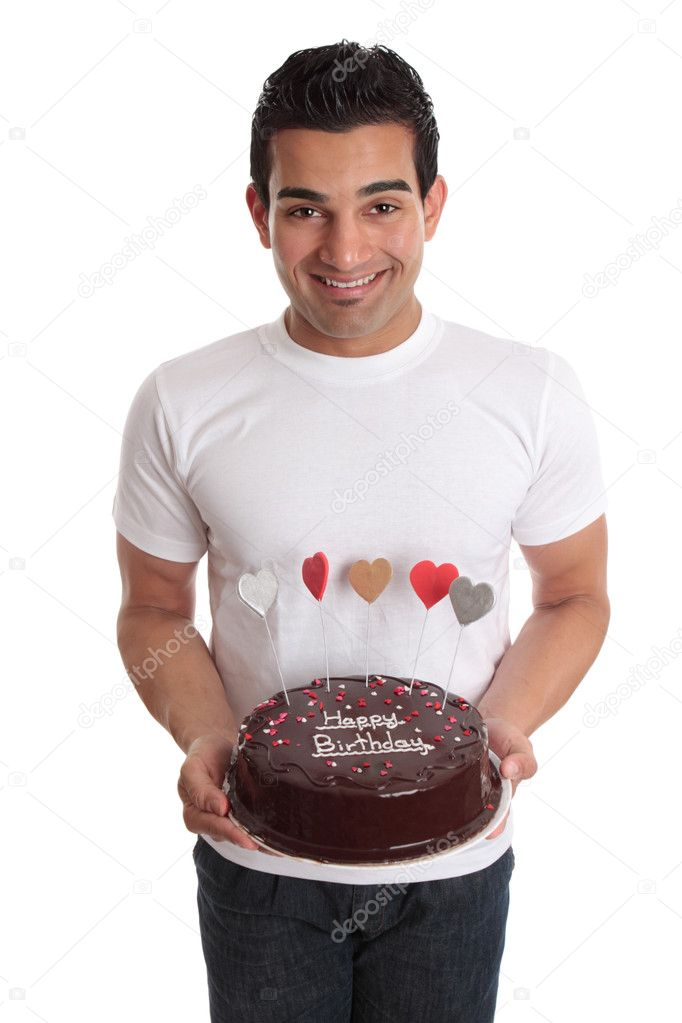A man carries a delicious chocolate cake decorated with iced hearts in colours of red, pink, gold, and silver.  Writing on cake - Happy Birthday - but could be   Stock Photo #2463651
