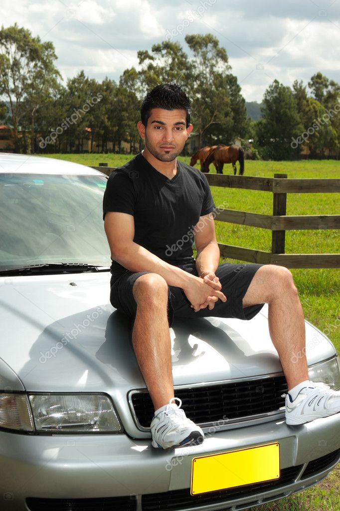 A casual dressed attractive man sitting on car bonnet of a silver sedan vehicle in the late afternoon.  Stock Photo #2463658