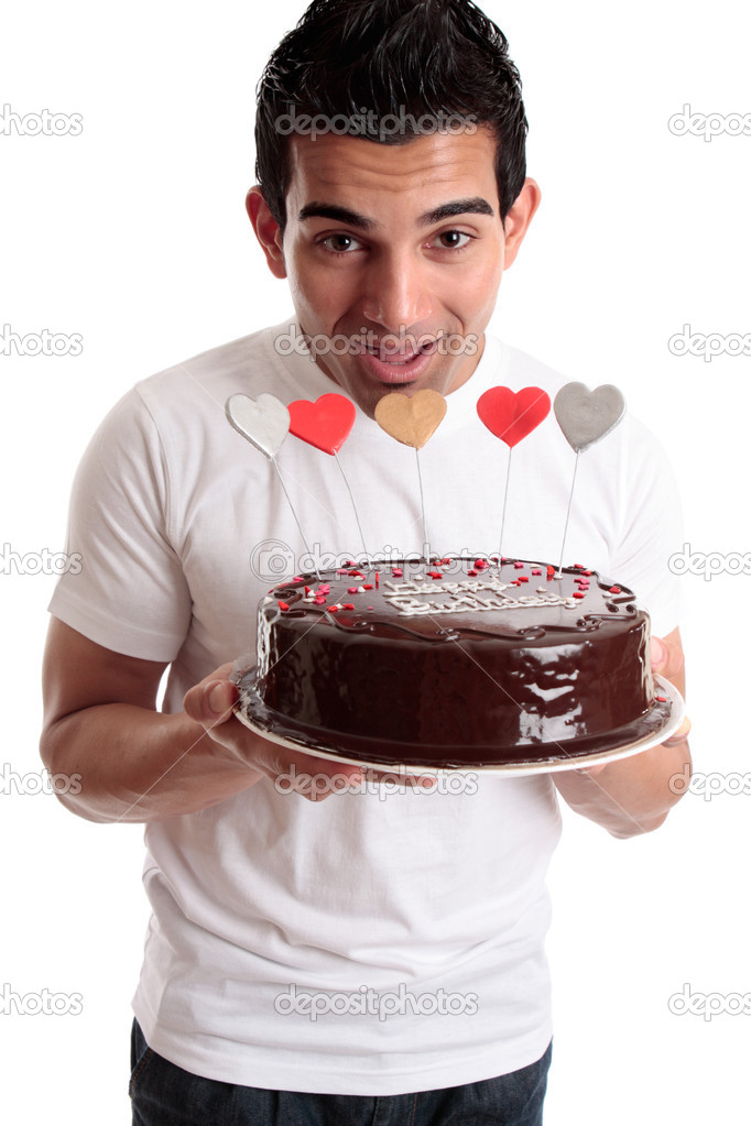 Cheeky male about to bite one of the hearts on a chocolate birthday cake  Stock Photo #2463672