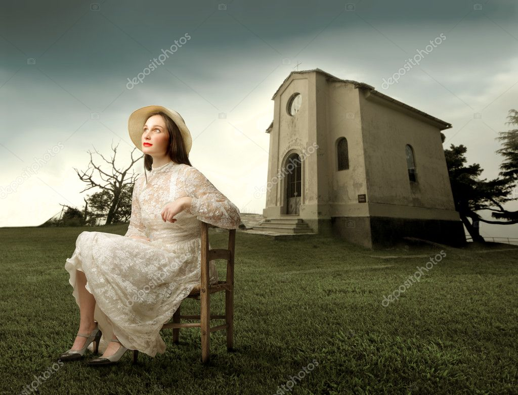 Bride sitting on a chair in a green meadow with a church on the background  — Stock Photo #2425197