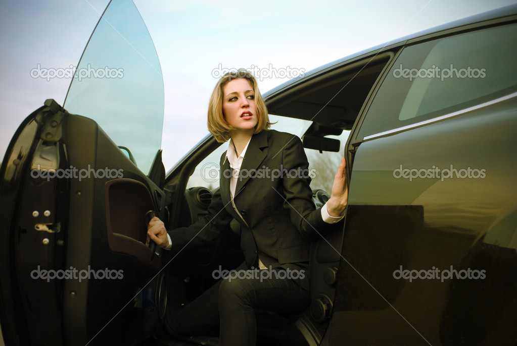 Portrait of a businesswoman coming out of a car  — Stock Photo #2425255