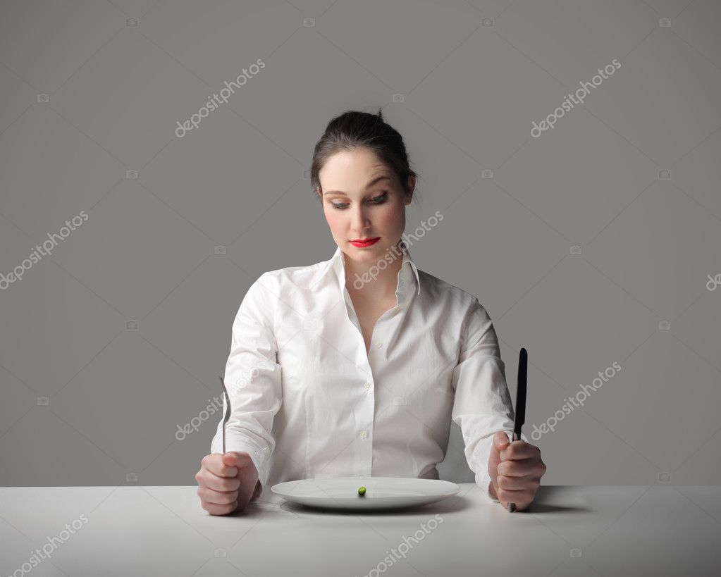 Portrait of a woman staring at a dish with a singular pea in it — Stock Photo #2488130