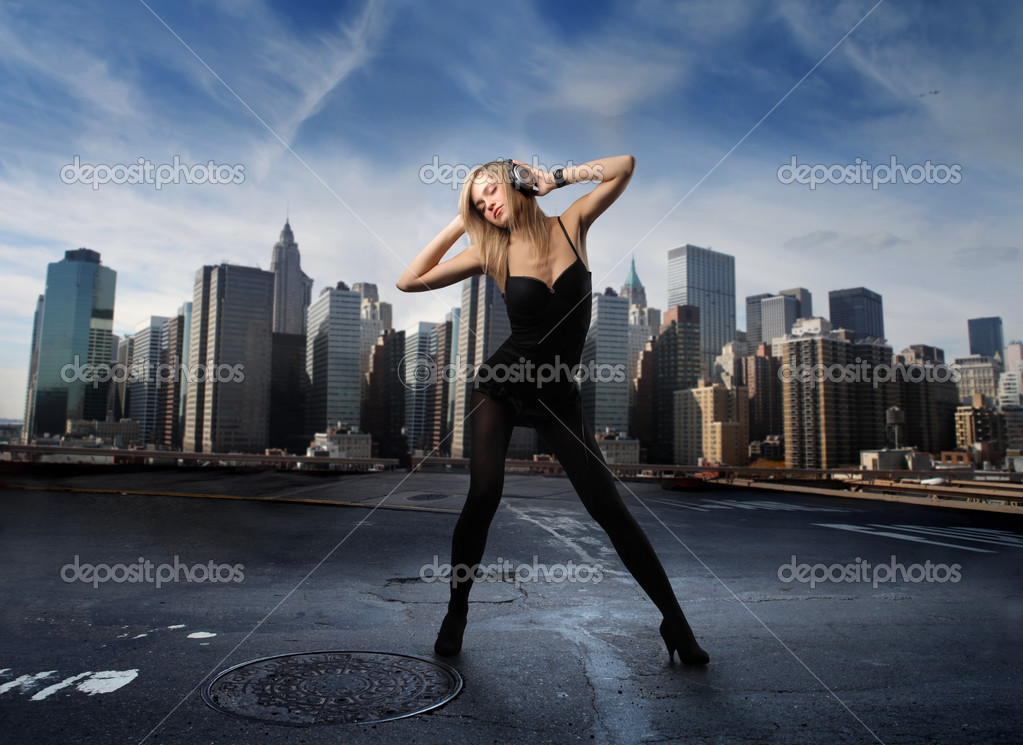 Portrait of a woman listening and dancing to music with cityscape on the background — Foto Stock #2488256