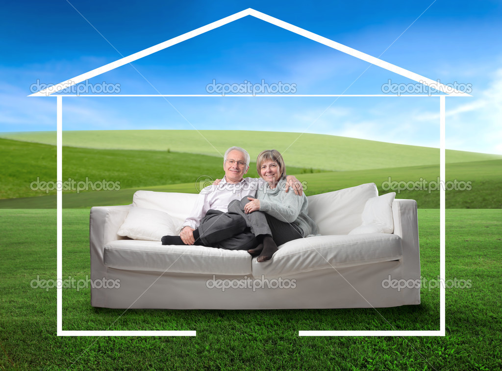 Portrait of a senior couple sitting in a couch on a green meadow and surrounded by the form of a house  Lizenzfreies Foto #2488290
