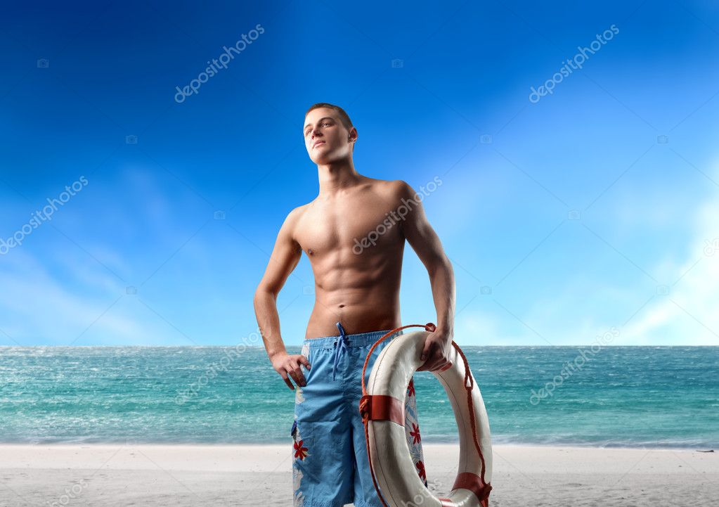 Portrait of a young man in swimsuit holding a lifesaver at the seaside — Stock Photo #2488814