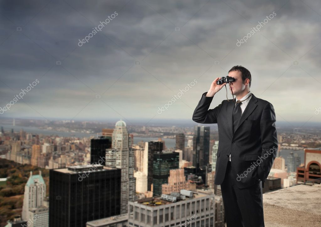 Portrait of a businessman standing on the top of a skyscraper and using a pair of binoculars — Stock Photo #2489188